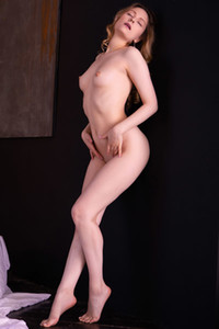 Alluring young dame poses naked giving us the perfect view of her feminine figure