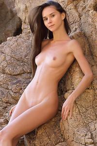 Long haired sweetheart enjoys posing naked on the beach