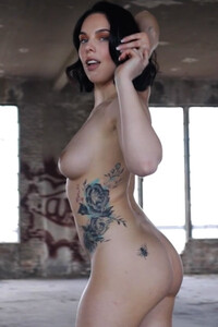 Blue eyed blooming dame evocatively posing as she gradually uncovers her tattoed figure